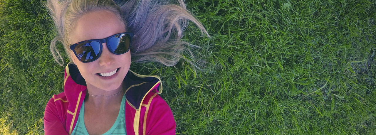 Woman in sun glasses lying in the grass and taking a selfie - Kari Traa