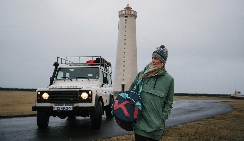 Woman walking carrying her Kari Traa bag with lighthouse in the background